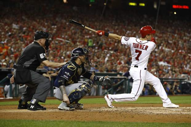 Washington Nationals Trea Turner, right, watches his solo home run in front of Milwaukee Brewers catcher Yasmani Grandal and umpire Mike Everitt in the third inning of a National League wild card baseball game, Tuesday, Oct. 1, 2019, in Washington. (AP Photo/Patrick Semansky)