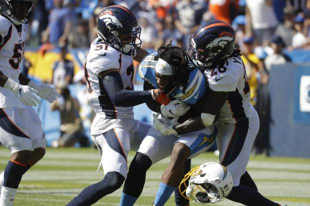 Denver Broncos free safety Justin Simmons, left, and cornerback Isaac Yiadom, right, tackle Los Angeles Chargers wide receiver Mike Williams as he looses his helmet during the first half of an NFL football game Sunday, Oct. 6, 2019, in Carson, Calif. (AP Photo/Alex Gallardo)