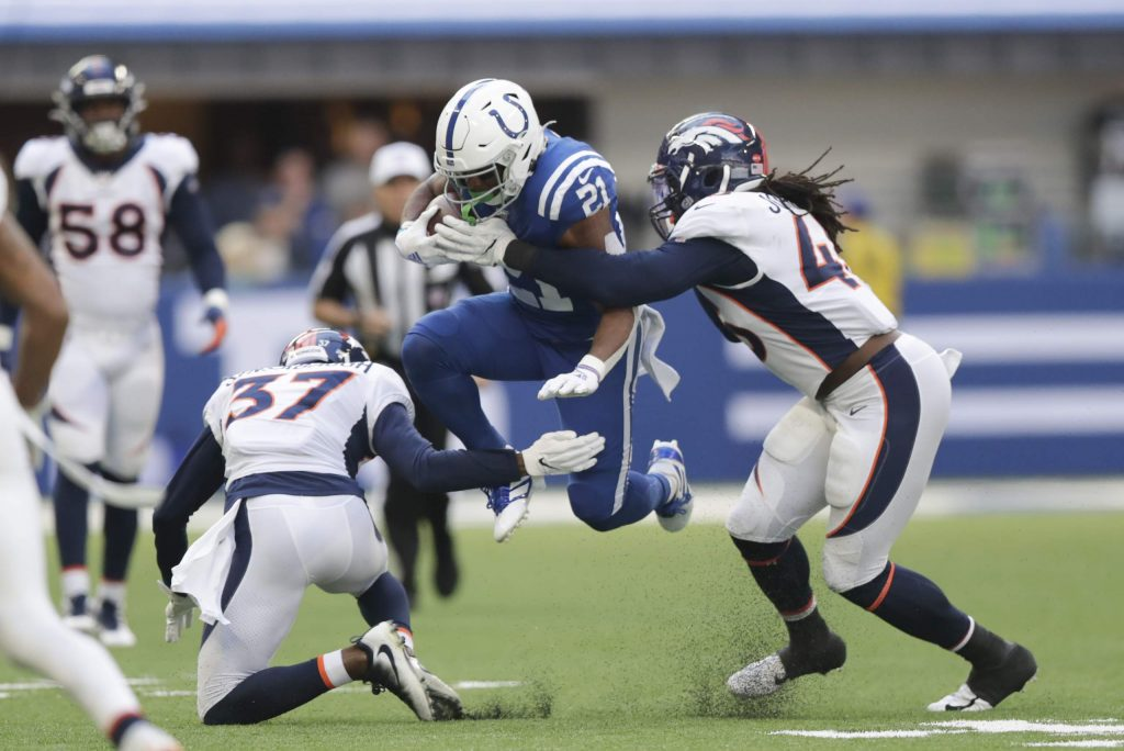 Indianapolis Colts' Nyheim Hines (21) is tackled by Denver Broncos' Coty Sensabaugh (37) and A.J. Johnson (45) during the first half of an NFL football game, Sunday, Oct. 27, 2019, in Indianapolis. (AP Photo/Michael Conroy)