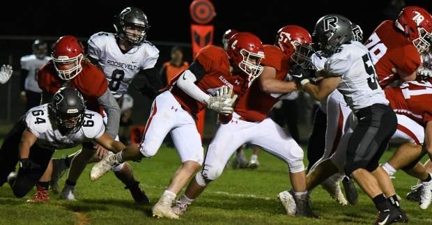 Glenwood Springs Demon Dylan Albright runs the ball around the defending Roosevelt Rough Riders during Friday night's game in Carbondale.