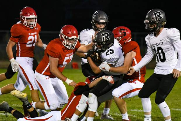 A Roosevelt Rough Rider tries to push through the defending Glenwood Springs Demons during Friday night's game in Carbondale.