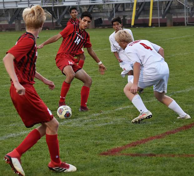 Glenwood Springs senior Angel Bernal tries to get around Steamboat Springs junior Devon John as Glenwood sophomore Reid Swanson looks on in the first half Tuesday at Stubler Memorial Field.