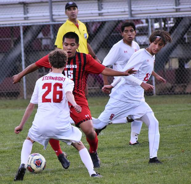Glenwood Springs junior Carlos Rodriguez tries to regain possession of the ball in the first half Tuesday at Stubler Memorial Field as Steamboat Springs junior Henry Cardillo (26) and junior Jack Clynes (right) defend.