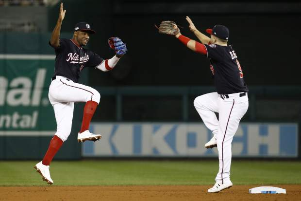 Washington Nationals' Victor Robles and Brian Dozier celebrate after Game 3 of the baseball National League Championship Series against the St. Louis Cardinals Monday, Oct. 14, 2019, in Washington. The Nationals won 8-1 to take a 3-0 lead in the series. (AP Photo/Patrick Semansky)