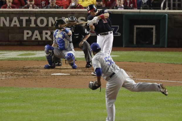 Washington Nationals' Ryan Zimmerman, back right, hits a three-run home run off Los Angeles Dodgers relief pitcher Pedro Baez (52) in the fifth inning in Game 4 of a baseball National League Division Series, Monday, Oct. 7, 2019, in Washington. Dodgers catcher Will Smith, back left, and umpire Doug Eddings, back center, look on. (AP Photo/Julio Cortez)