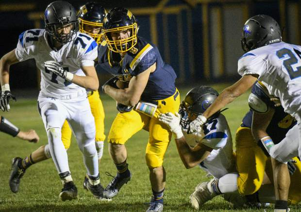 Rifle's Levi Warfel drags Coal Ridge defender Jackson Wade as he splits the Titans defense on his way to the endzone in the second quarter.