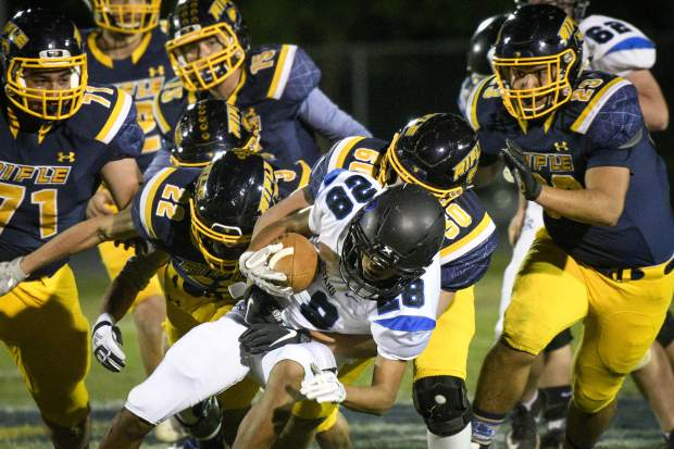 The Rifle defense swarms Coal Ridge's Danny Salas in the third quarter of the Bears 44-0 trouncing of the Titans Friday at Bear FIeld.