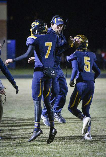 Rifle's Holden Stutsman celebrates with one of his coches after scoring on a quarterback sneak in the second quarter.