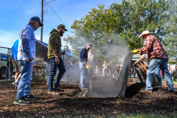A group of men unearth the slow-cooked pit barbecue meat and potatoes at the 110th annual Carbondale Potato Day festival Saturday morning at Sopris Park.
