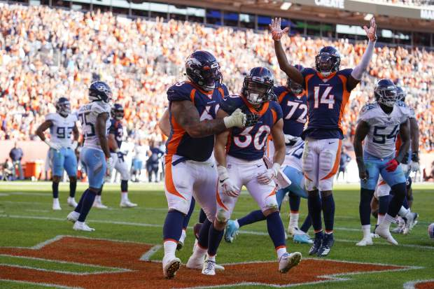 Denver Broncos running back Phillip Lindsay (30) reacts with teammates after scoring a touchdown during the second half of an NFL football game against the Tennessee Titans, Sunday, Oct. 13, 2019, in Denver. (AP Photo/Jack Dempsey)