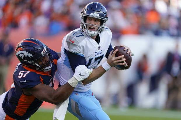 Denver Broncos defensive end DeMarcus Walker, left, hauls down Tennessee Titans quarterback Ryan Tannehill during the second half of an NFL football game Sunday, Oct. 13, 2019, in Denver. (AP Photo/Jack Dempsey)