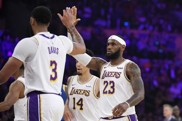 Los Angeles Lakers forward LeBron James congratulates forward Anthony Davis during a timeout in the first half of the team's preseason NBA basketball game against the Golden State Warriors on Wednesday, Oct. 16, 2019, in Los Angeles. (AP Photo/Mark J. Terrill)