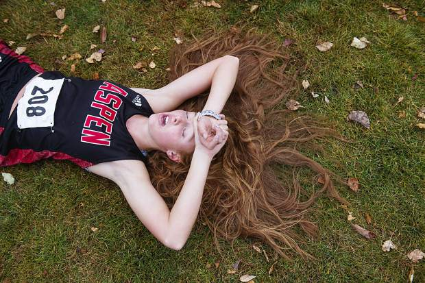 Aspen High School's Edie Sherlock lays on the ground catching her breath Friday after she competed in the 2019 Class 3A regional cross country meet at Crown Mountain Park in El Jebel. For more coverage of the meet, go to page XXXX.