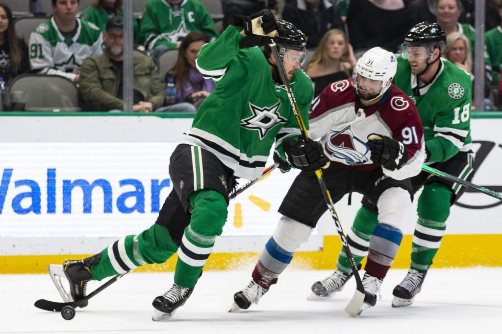 Colorado Avalanche center Nazem Kadri (91), Dallas Stars center Jason Dickinson (18) and defenseman Jamie Oleksiak (2) battle for the puck during the second period of an NHL hockey game in Dallas, Tuesday, Nov. 5, 2019. (AP Photo/Sam Hodde)