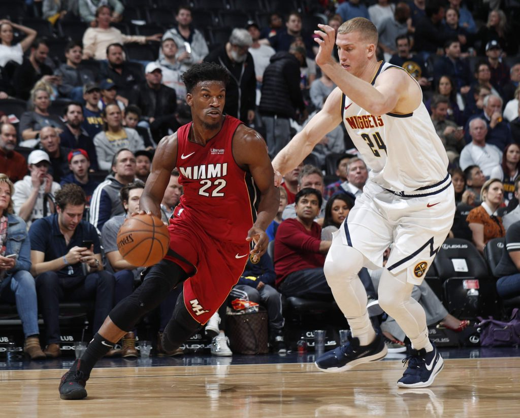 Miami Heat forward Jimmy Butler, left, drives past Denver Nuggets center Mason Plumlee in the first half of an NBA basketball game Tuesday, Nov. 5, 2019, in Denver. (AP Photo/David Zalubowski)