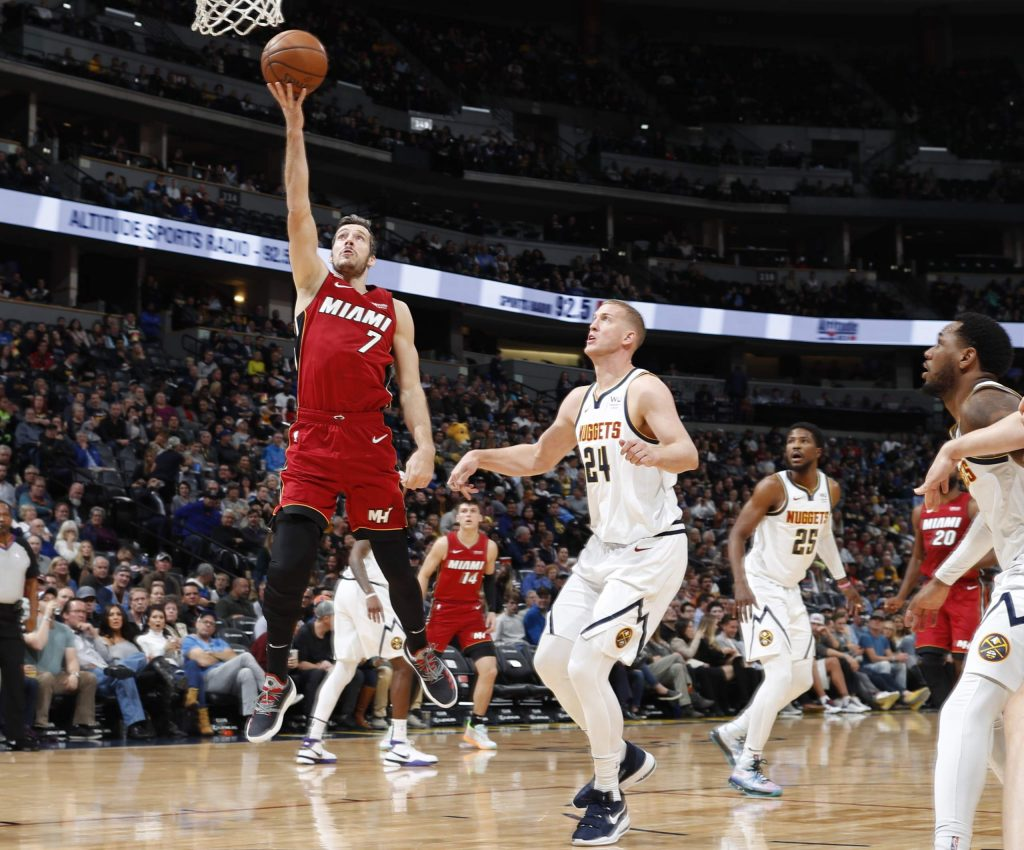 Miami Heat guard Goran Dragic, left, drives the lane for a basket past Denver Nuggets center Mason Plumlee in the first half of an NBA basketball game Tuesday, Nov. 5, 2019, in Denver. (AP Photo/David Zalubowski)