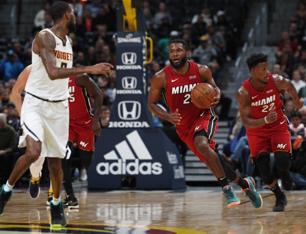 Miami Heat forward Justise Winslow, right, picks up a loose ball as Denver Nuggets forward Will Barton drops back to defend in the first half of an NBA basketball game Tuesday, Nov. 5, 2019, in Denver. (AP Photo/David Zalubowski)