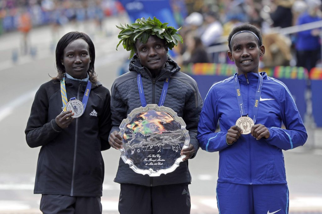 New York City Marathon women's winner Joyciline Jepkosgei, center, of Kenya, is flanked by second finisher and country mate Mary Keitany, left, and third finisher Ruti Aga, of Ethiopia, as they pose for photos in New York's Central Park, Sunday, Nov. 3, 2019. (AP Photo/Richard Drew)