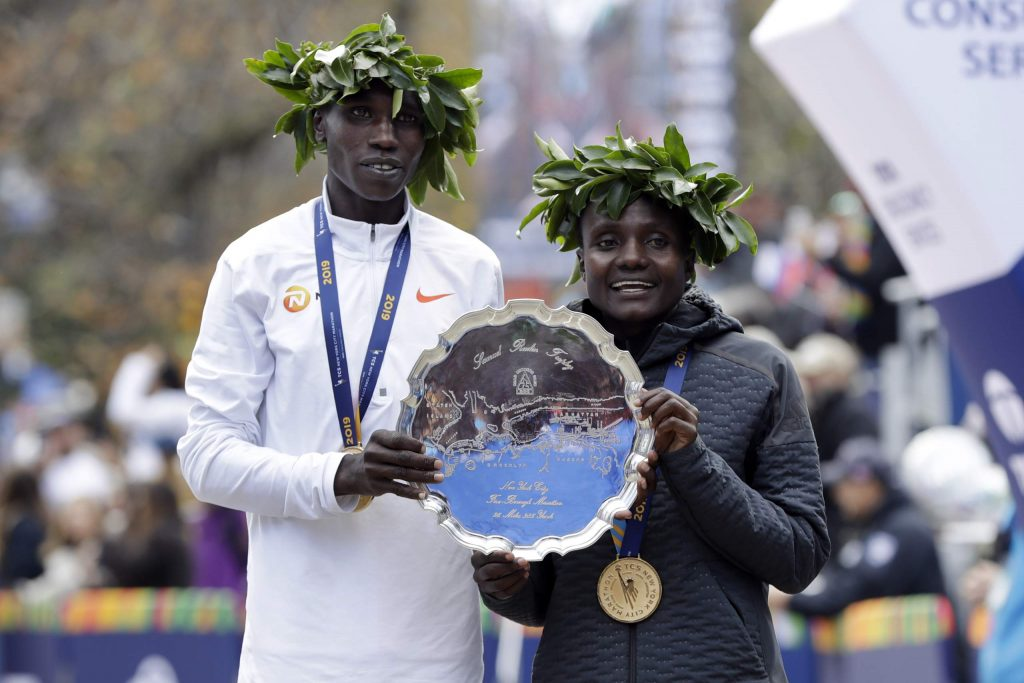 Geoffrey Kamworor, left, and Joyciline Jepkosgei, both of Kenya, pose for photos as the men's and women's winners of the New York City Marathon, in New York's Central Park, Sunday, Nov. 3, 2019. (AP Photo/Richard Drew)