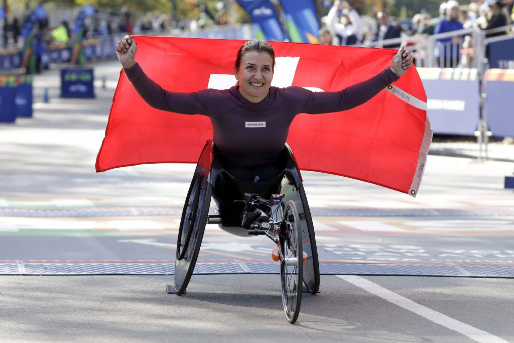 Manuela Schar, of Switzerland, poses for photos as the winner of the pro wheelchair women's division of the New York City Marathon, in New York's Central Park, Sunday, Nov. 3, 2019. (AP Photo/Richard Drew)