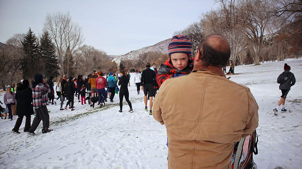 Brian Gibson carries Ethan Gibson as they make their way to the starting line for the 33rd annual Glenwood Springs Turkey Day 5K on Thursday.