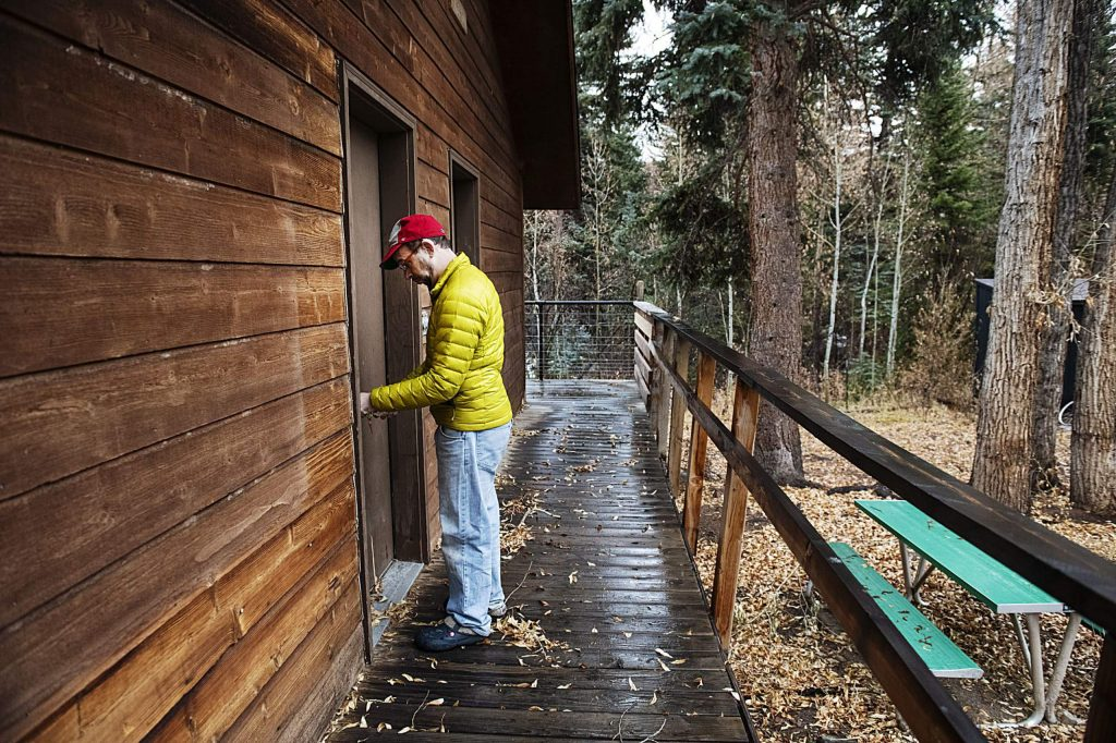 Eric Kaika unlocks the door to one of the many rooms available to campers on the Aspen Camp property in Old Snowmass on Thursday, Nov. 21, 2019. (Kelsey Brunner/The Aspen Times)