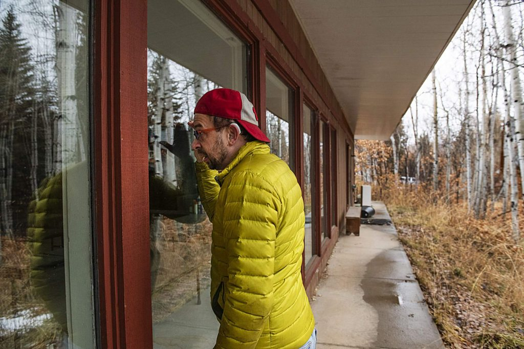 Eric Kaika peeks through the window of the main lodge on the property of the Aspen Camp of the Deaf and Hard of Hearing on Thursday, Nov. 21, 2019. (Kelsey Brunner/The Aspen Times)