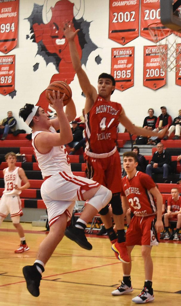 Glenwood Springs senior John Iuele takes it to the hoop against Montrose defender Trey Schwerdtfeger during the Demons 38-36 win over the Indians in the Demon Invitational back in early December.