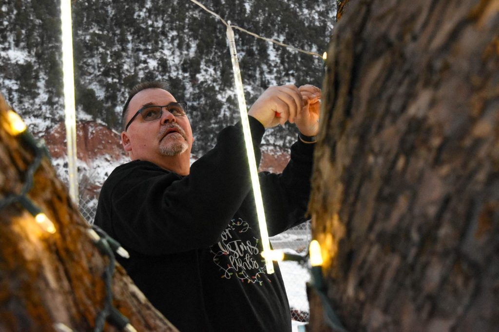 Paul Carlson checks on a section of Christmas lights hanging in the yard of his Canyon Creek home.