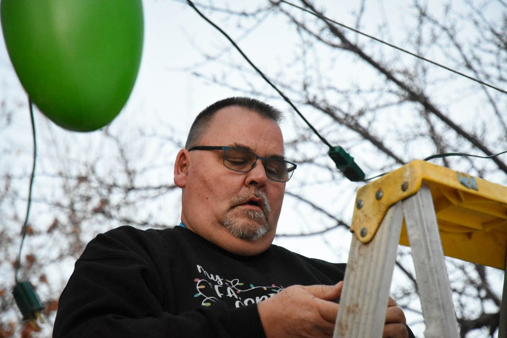 Paul Carlson works to hang more  Christmas lights in the yard of his home in Canyon Creek.
