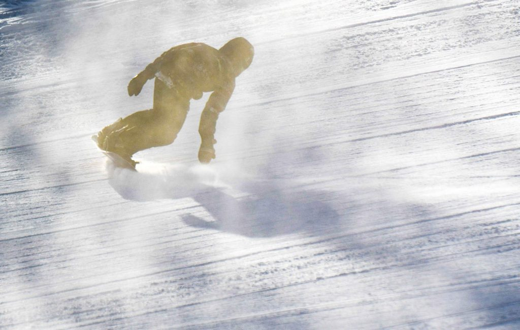 A snowboarder rides the toe edge through a cloud of snow on opening morning at Sunlight Mountain Resort on Dec. 6th.