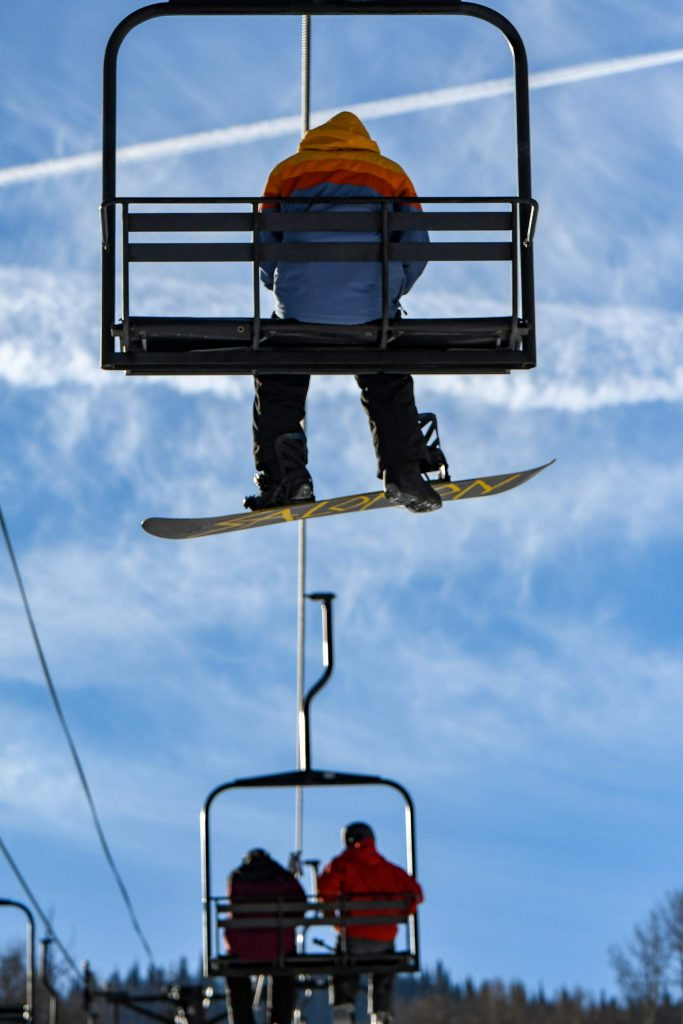 Skiers and snowboarders make their way up the mountain on the lift on opening morning at Sunlight Mountain Resort.