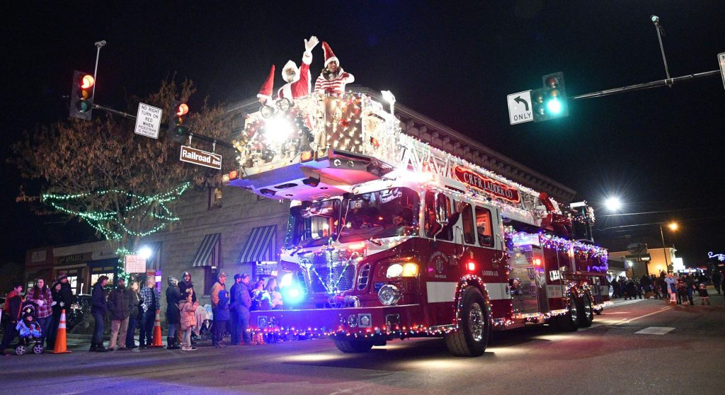 Santa Claus waves to the crowd as he gets a lift from Colorado River Fire Rescue during the annual Parade of Lights.