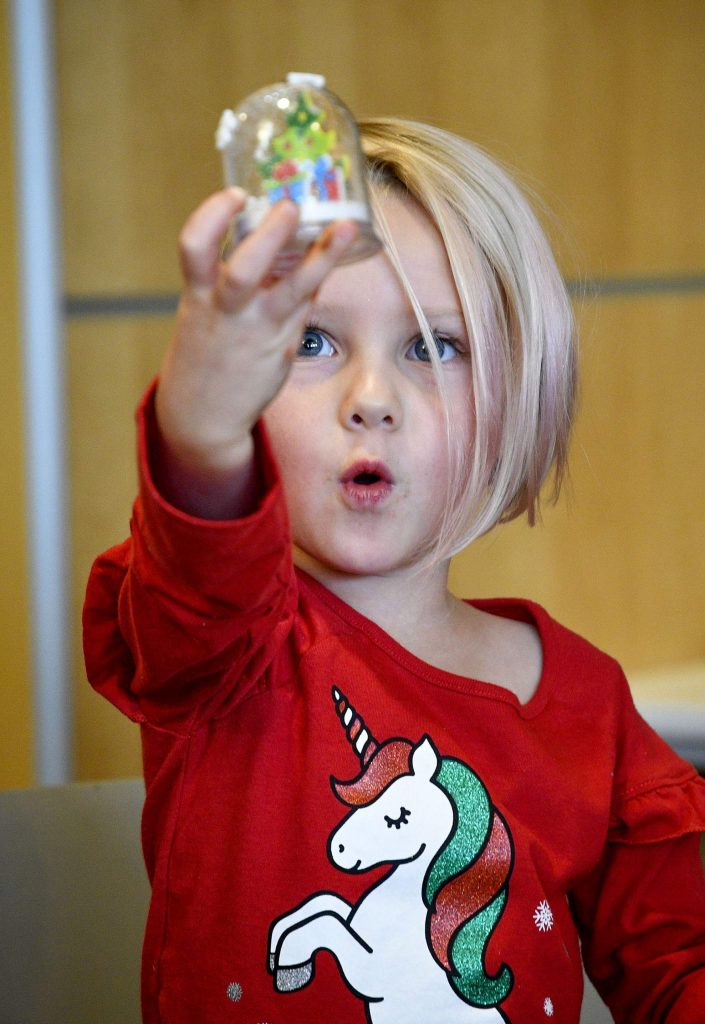 Lana Stewart, 4, of RIfle takes a look at her completed snow globe that she made with a little help from her mom Cathy Stewart at the Rifle Library last Saturday.
