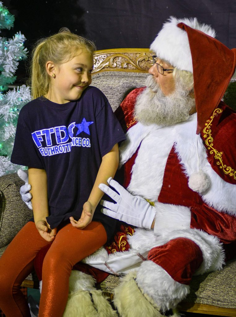 Santa Claus talks with one of many children he visited during his stop at the Ute Theater in Rifle last weekend.