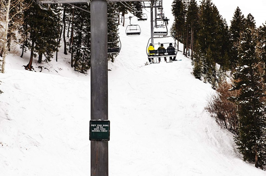 Skiers ride by tower 10 on the Exhibition Lift at Aspen Highlands on Thursday. A sign alerts riders they are entering the White River National Forest.