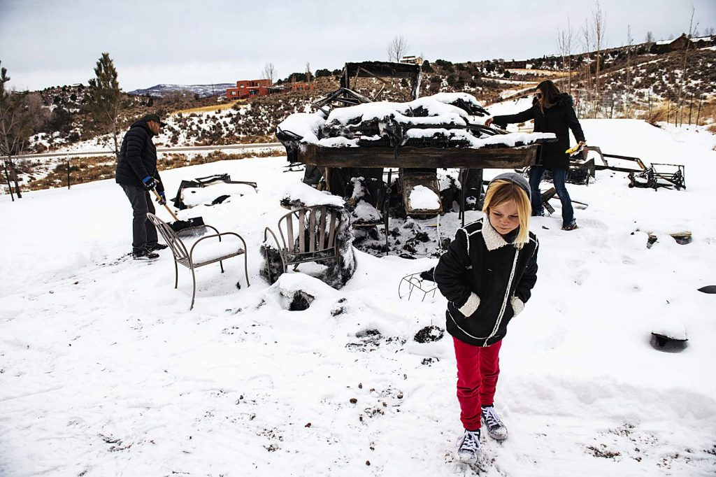 Jake Zamansky, left, and his wife Tara Dakides clean up the area around their burnt fifth-wheel RV as their daughter Meadow Anne Franklin Dakides Zamansky walks out of the snow on their property in Carbondale on Sunday, December 15, 2019. The children expressed that they loved living in the RV. Tara said that it was nice to feel like they had a home to feel settled in.