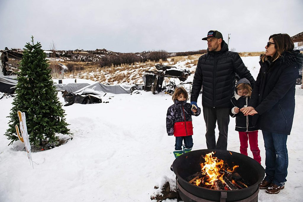 Jake Zamansky and Tara Dakides stand with their children Bowie Alan Dakides Zamansky, 4, left, and Meadow Anne Franklin Dakides Zamansky, 6, center right, next to a fire pit on their property in Carbondale on Sunday, December 15, 2019. The family lost their fifth-wheel RV to a fire believed to be caused by a generator and makeshift skirting on the outside of the RV. The family was off the property when the fire started.