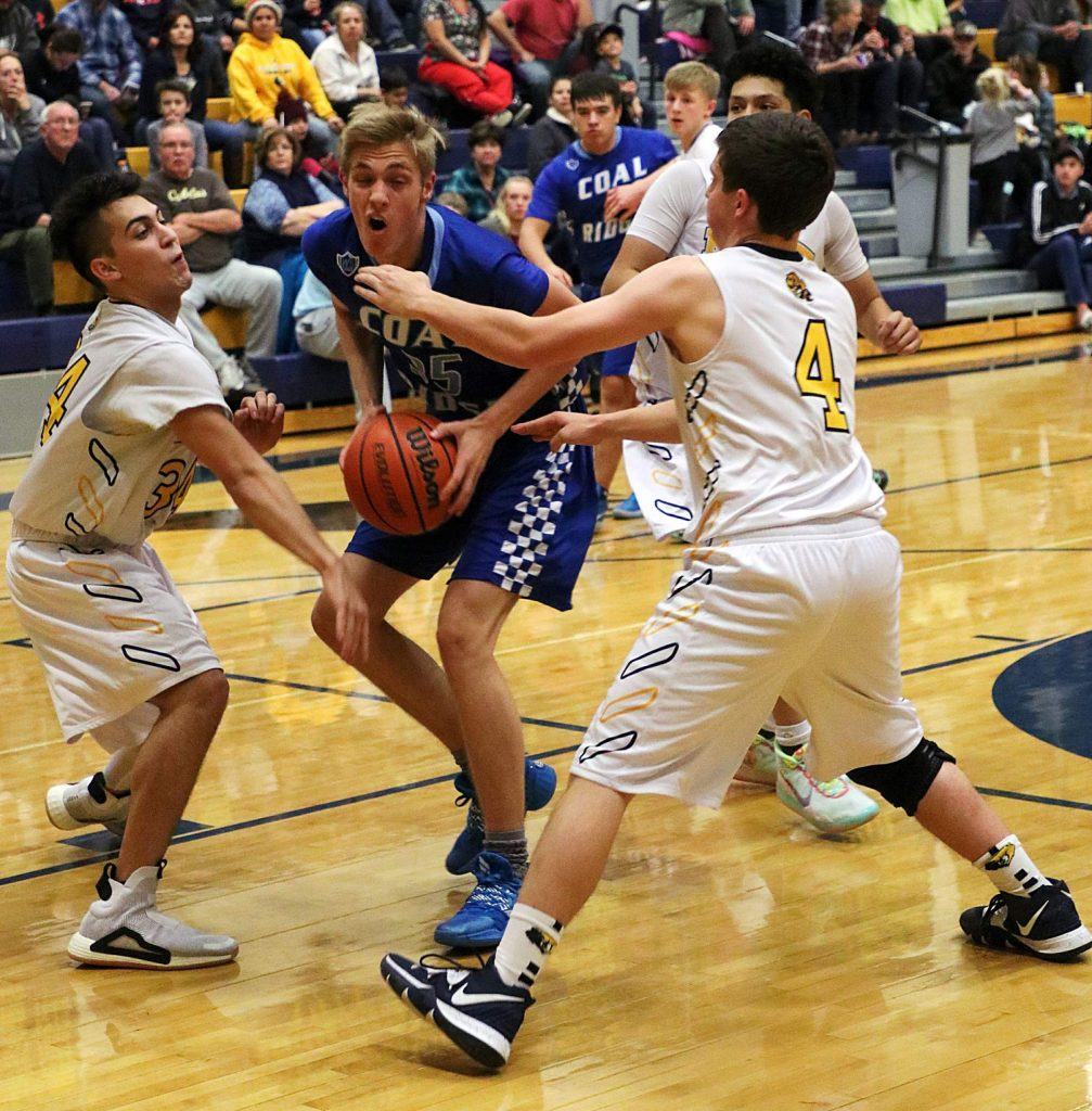 Coal Ridge junior Hank DiMarco looks for an opening in the lane against the Rifle defense, in the Titans' 52-25 win over the Bears at Rifle High School Tuesday night.