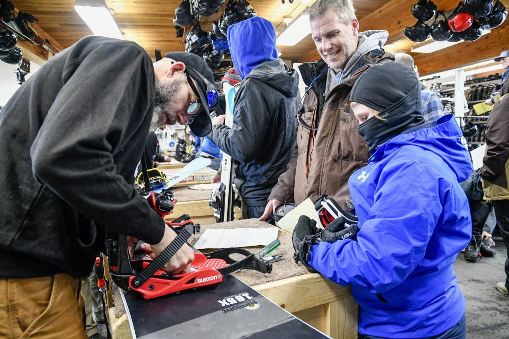Sunlight rental shop tech Brett Marshall fits a pair of binds for Jason Ainsworth and his son Liam, 9, of Castle Rock as riders and skiers take advantage of the $20 lift tickets last Friday.