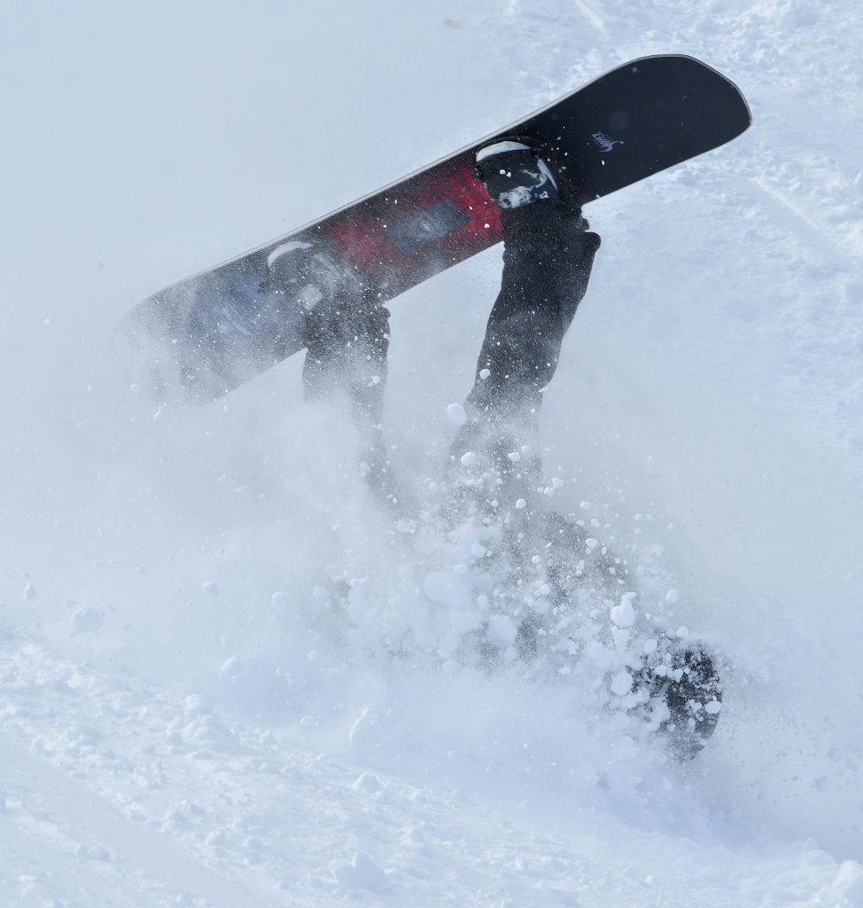 A snowboarder crashes into the soft snow after trying a backflip of a jump near Sun King.