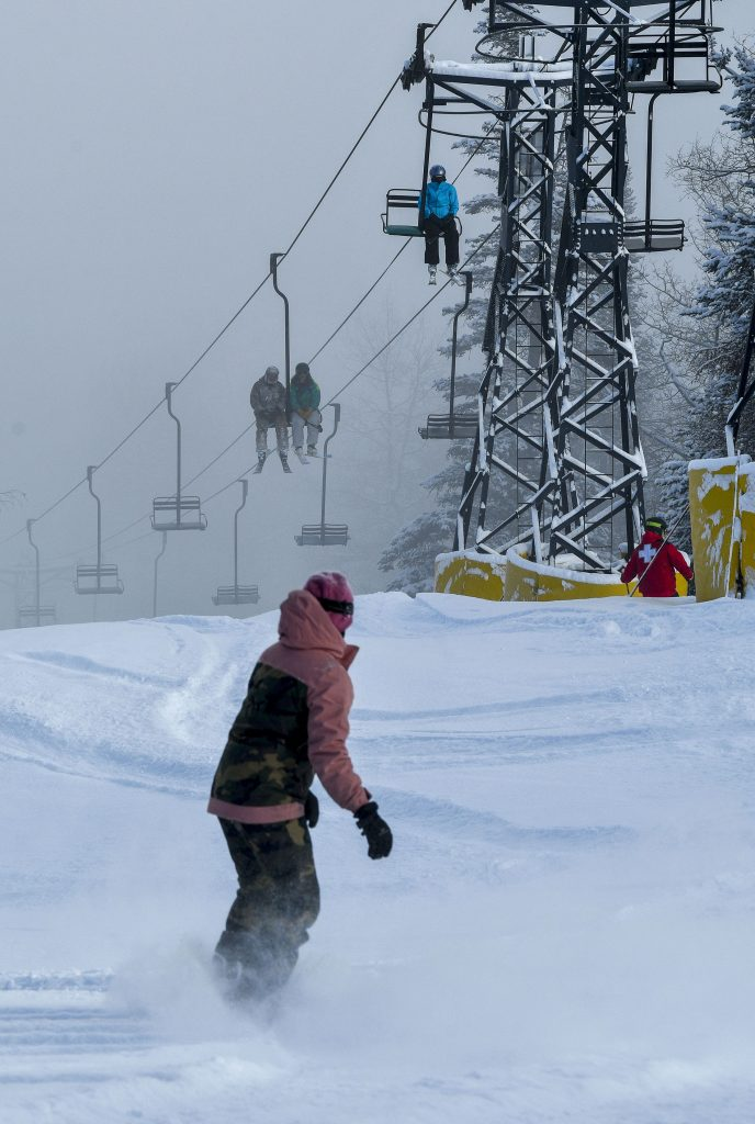 A snowboarders carves some lines in the fresh un the powder near the top of the Segundo lift last Friday.