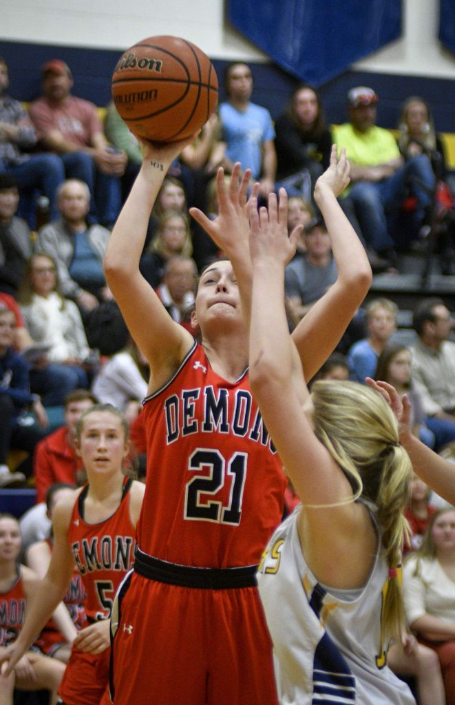 Glenwood's Graci Dietrich takes a shot over Rifle's Taylor Davis late in the third quarter Friday in Rifle. The Demons handled the Bears 52-17 in the conference matchup.