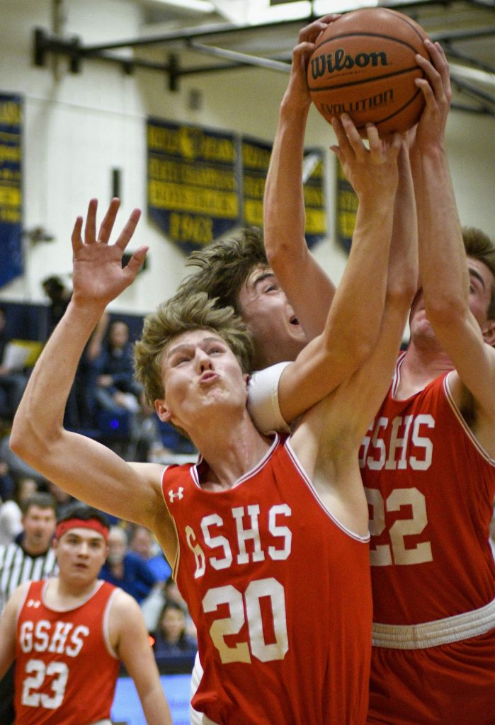 Glenwood's Adam Schrader (20) and Will Narvaez (22) battle for the rebound with Rifle's Kade Bishop during second-quarter action Friday in Rifle.