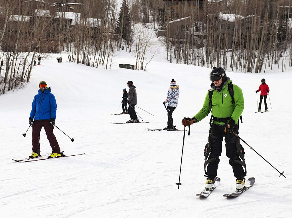 Jim Harris, 38, right, skis down fanny hill at Snowmass to start his day skiing with the ROAM Robotics Elevate exoskeleton on Friday, Jan. 31, 2020. Harris had tried the exoskeleton once before and said it was one of the best days of skiing he'd had since his accident five years prior. Harris had a snow kite accident during a ski expedition in Patagonia. He broke nine of his vertebrae and was paralyzed from the sternum down. After working with Craig Hospital, he regained movement. He said that he was still not as fast as he had wanted to be nor was his stamina good enough to keep him on the mountain for more than five to seven runs. (Kelsey Brunner/The Aspen Times)