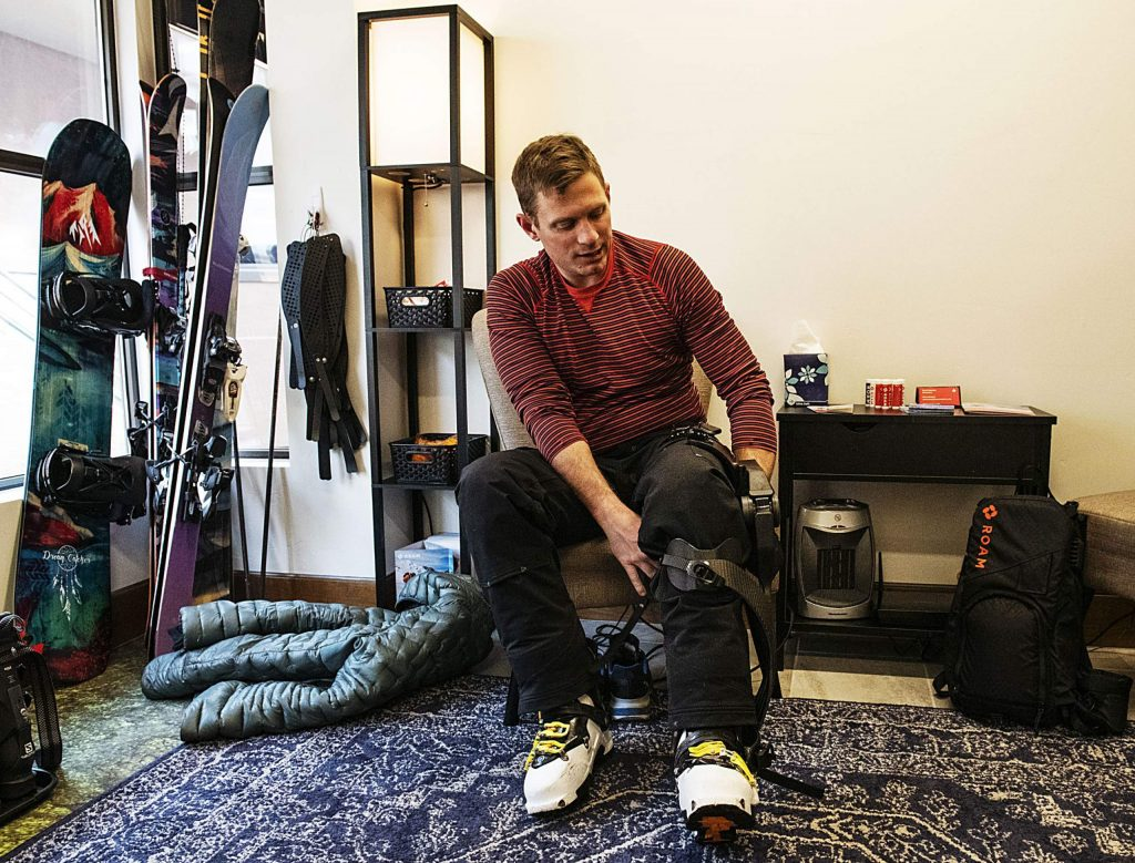 "Jim Harris puts on the left leg to the ROAM Robotics Elevate exoskeleton on Friday, Jan. 31, 2020. Harris said that he noticed a huge difference with his skiing once he turned the exoskeleton off. ""I really appreciate this, because maybe I'll feel a little faster and aligned with my own ability,"" Harris said of the exoskeleton. (Kelsey Brunner/The Aspen Times)"