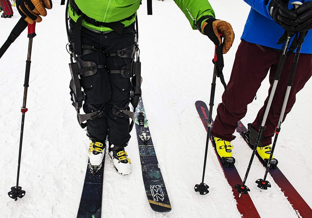 """Jim Harris, left, and ROAM Director of Marketing Johnny Kern prepare to ski to the Village Express lift in Snowmass on Friday, Jan. 31, 2020. """"I'm really just excited to get some time on crazy robot ski legs,"""" said Harris of the ROAM Robotics Elevate exoskeleton. (Kelsey Brunner/The Aspen Times)"""