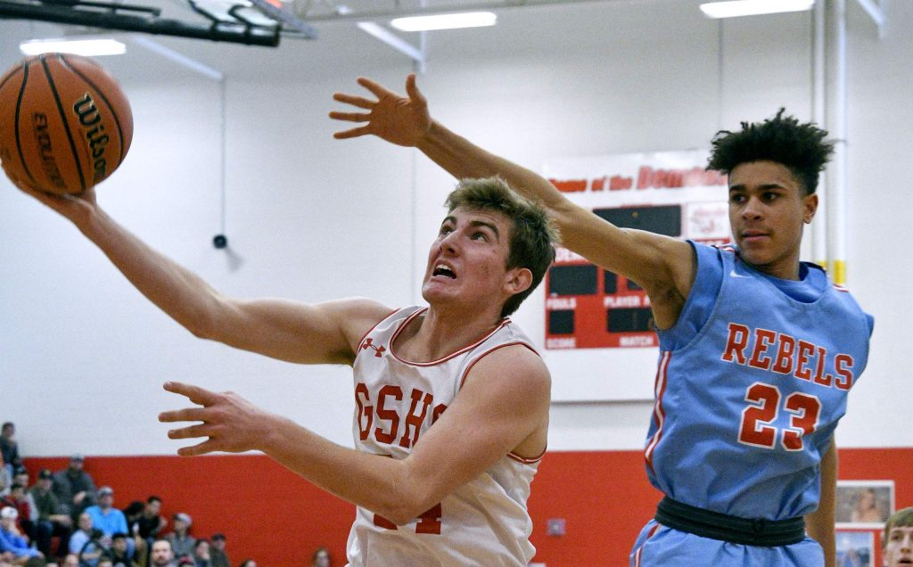 Glenwood's Blake Nieslanik alters his shot under the defensives pressure from Weld Central's Bryce Andrews during third quarter action Saturday. The Demons defeated the Rebels 55-30 to advance in the 4A playoffs.
