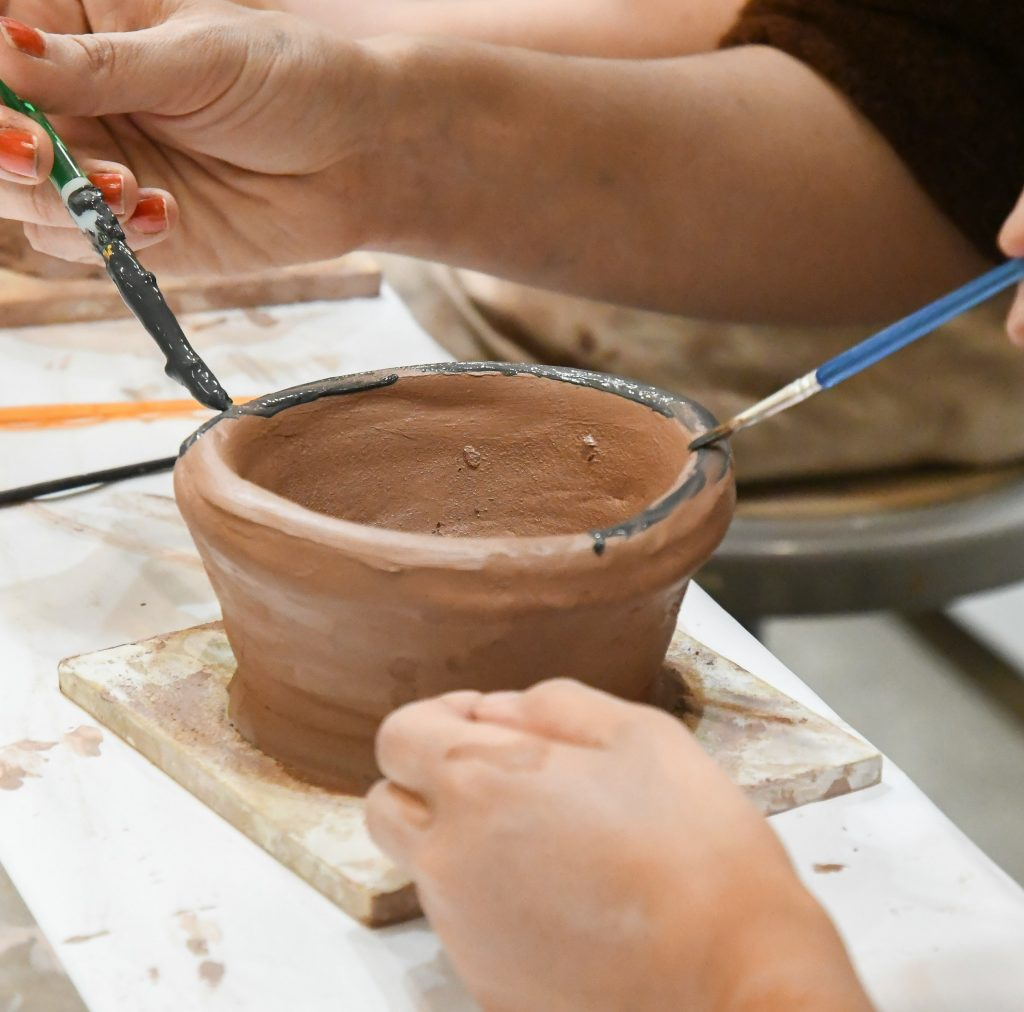 A big buddy and little buddy work together to paint a bowl they made during Monday night's pizza and pottery gathering. Buddy Program