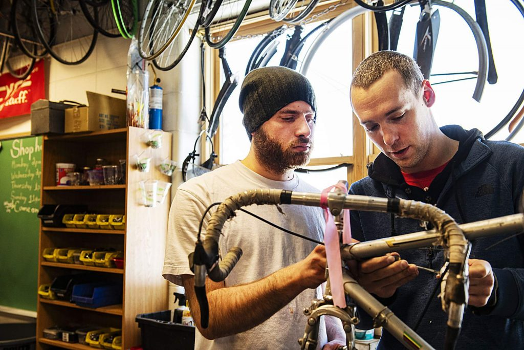 Zachary, left, and Ascendigo coach Jon Kiningham work to take a part a bike in the Way of Compassion bicycle project shop on Thursday, Feb. 13, 2020. Kiningham and Zachary have been working together a week. Ascendigo is a nonprofit in the Roaring Fork Valley that works to empower people with Autism Spectrum Disorder through different services.(Kelsey Brunner/The Aspen Times)